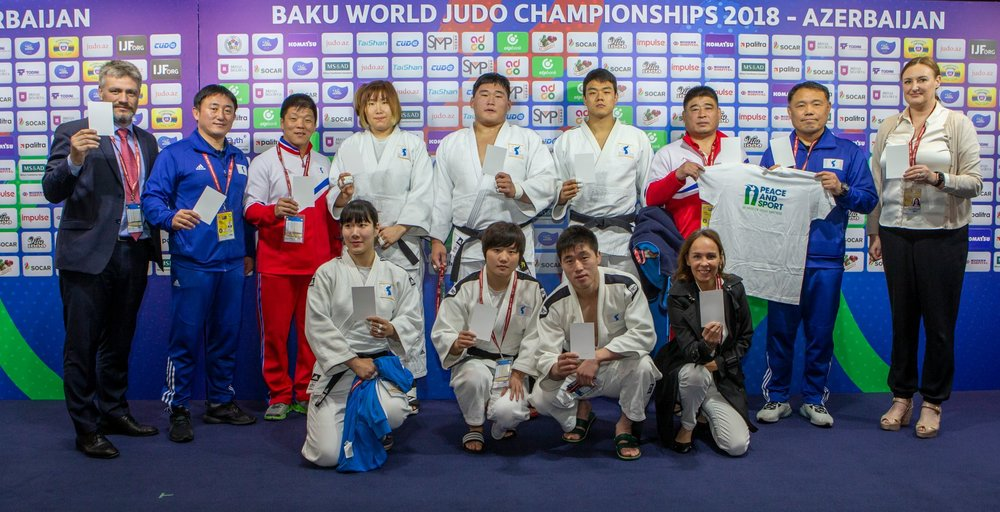 Flanked by IJF officials, a united Korean team raises a white card Thursday as a symbol of peace // IJF