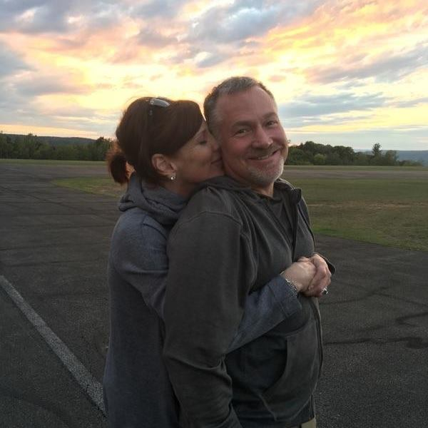 Dr. Criscione with his wife hugging him from behind while sun sets.