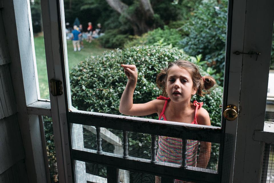 Girl looking through screen door