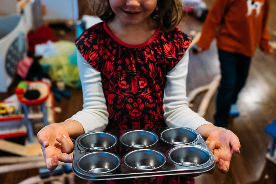 Little girl holding an empty muffin tin.