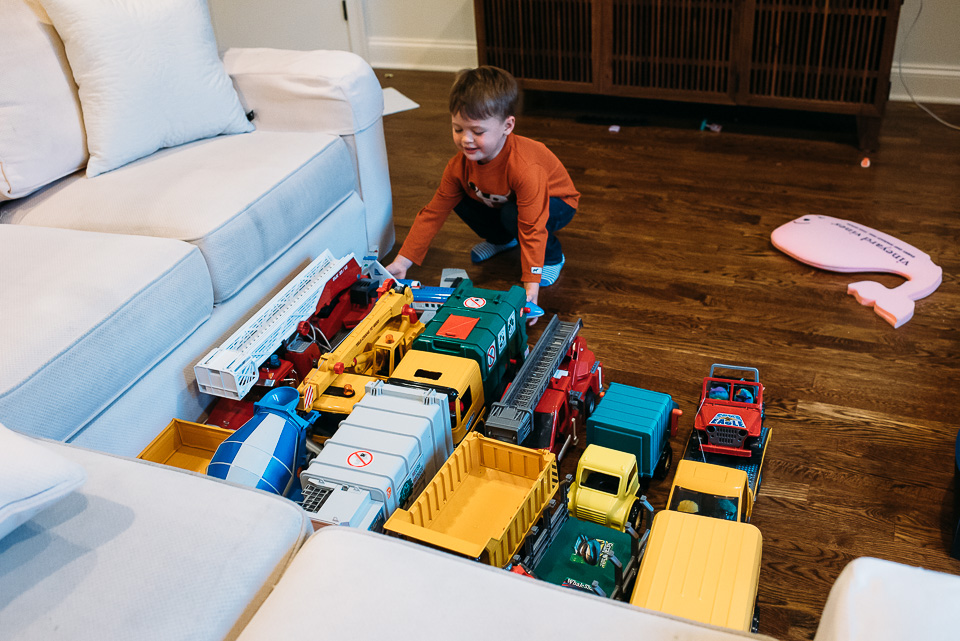 Boy arranging his toy trucks in rows.