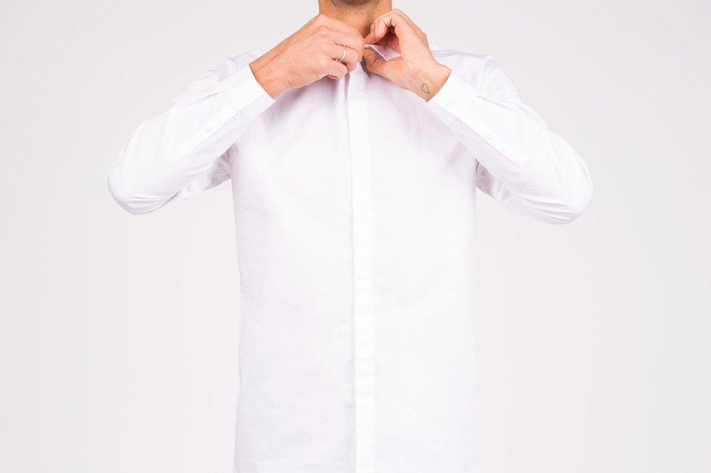 Man buttoning crisp white dress shirt