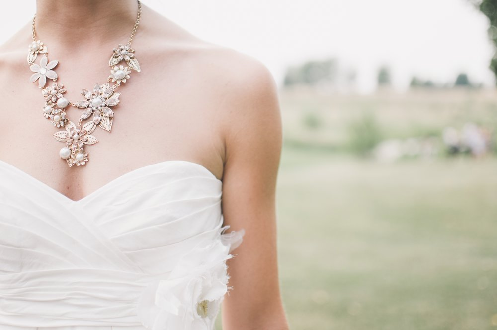 close up of whit wedding dress and elaborate necklace