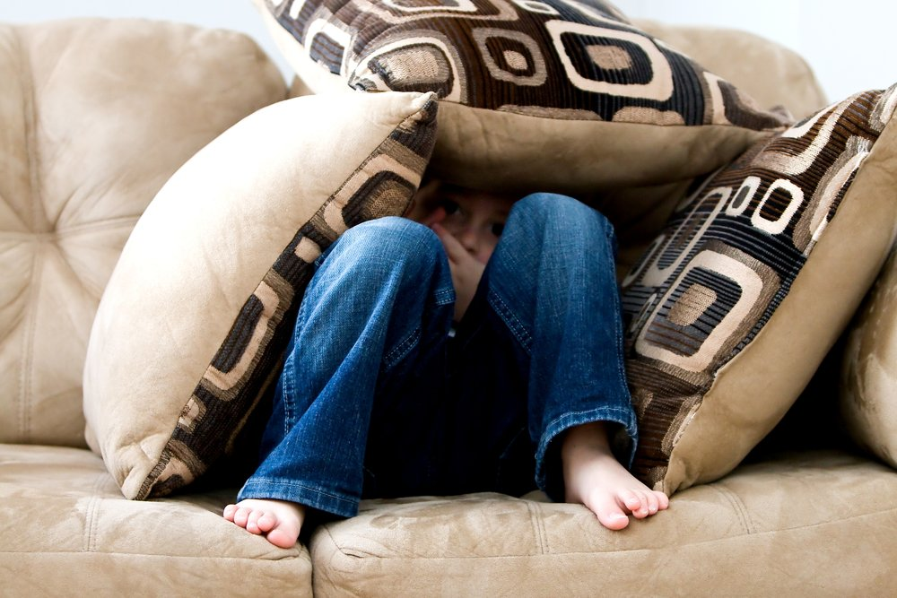 Child hiding in pillows on couch.