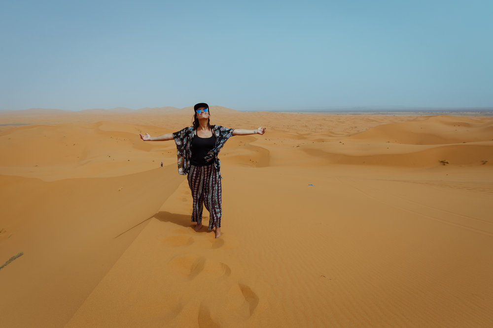 Happy in the noon sun on the giant sand dunes of Merzouga.