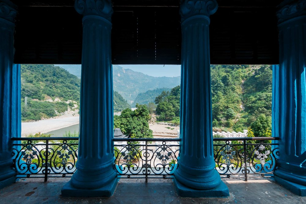 The palace's distinct blue pillars overlooking the river landscape.