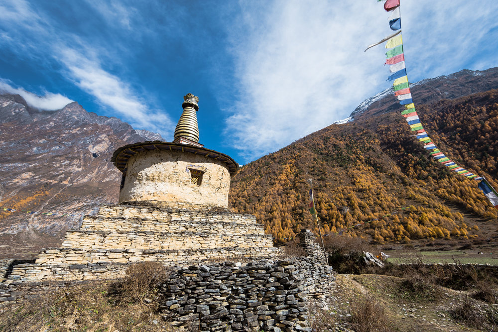 A Tibetan Buddhist stupa set in the middle of a vast valley.