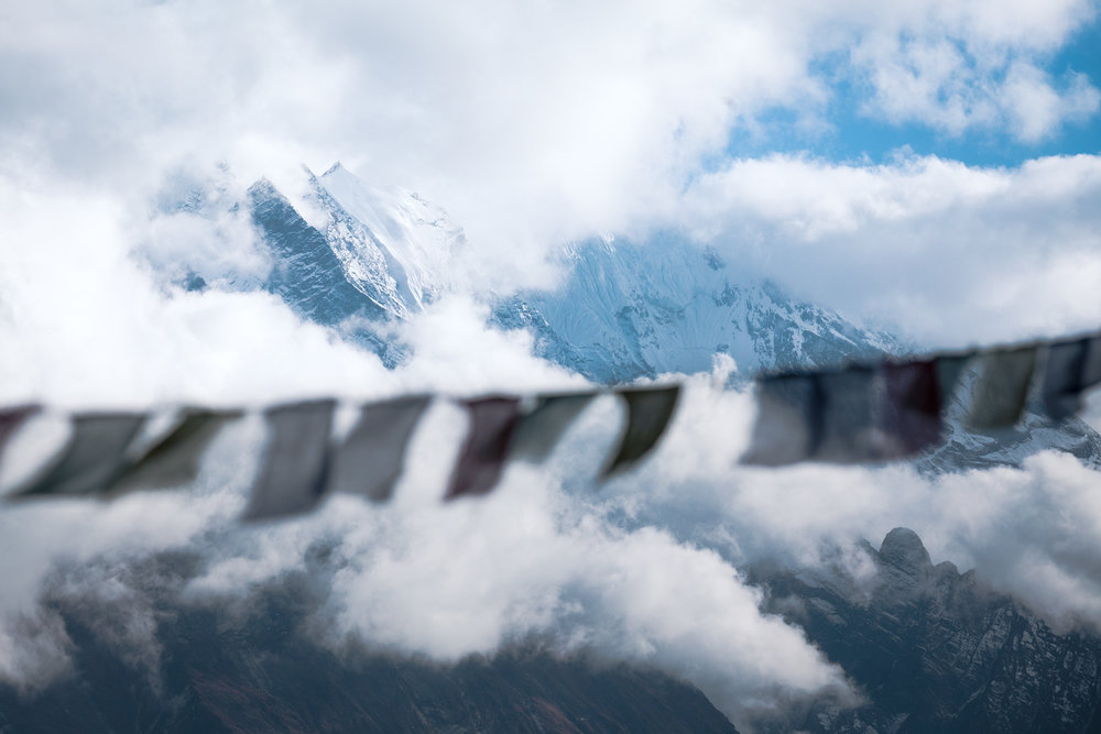 Prayer flags blow in the breeze atop Mu Gompa overlooking Tsum Valley.