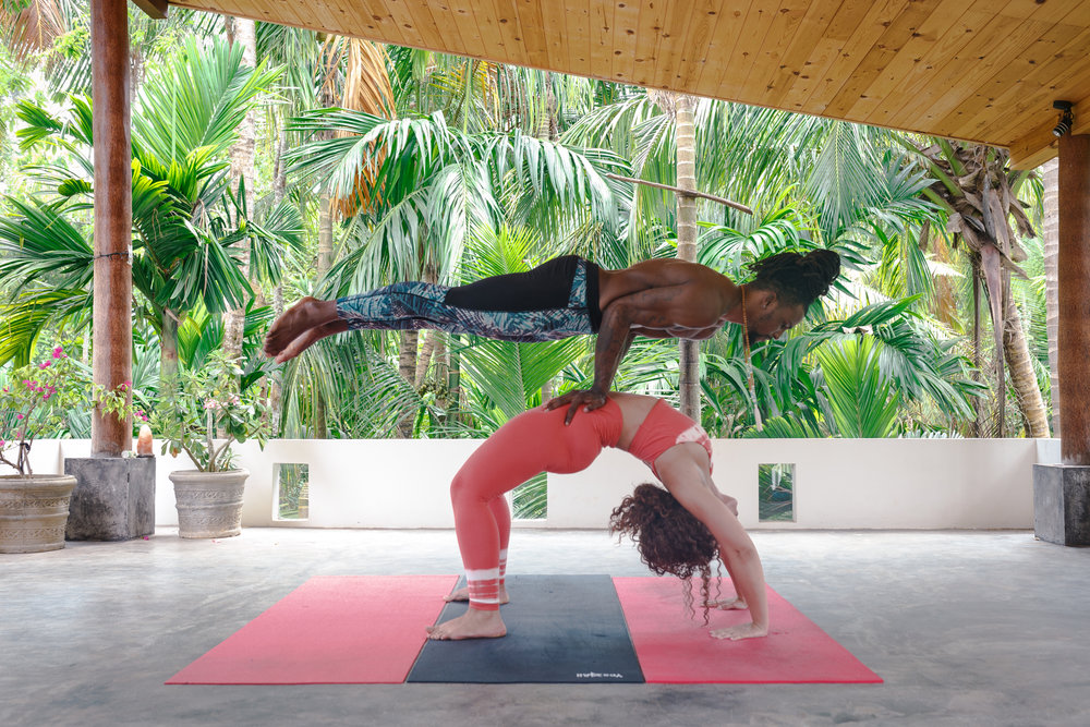 DJ and Iysha practicing acro-yoga in the yoga shala.