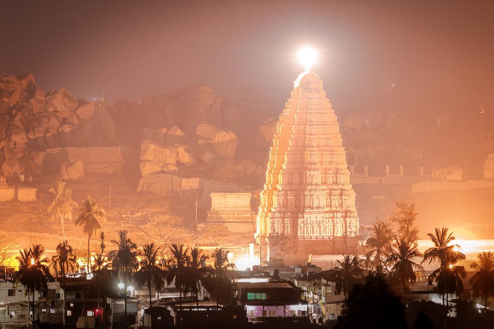 The Virupaksha Temple illuminated at night.