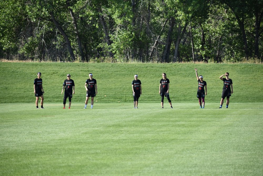 Washington DC Scandal 's captain, Molly Roy, raises her hand to signal the O-Line ready for the pull from  Denver Molly Brown  in a quarterfinals game on Sunday at the Colorado Cup.