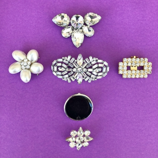 Pearl earring, diamante broaches, black button and a gold shoe clip