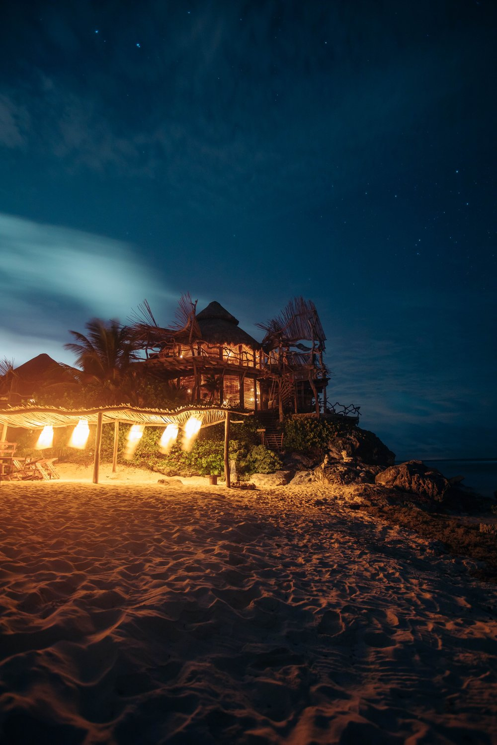 tiki style hut hotel in the sand on a beach at night