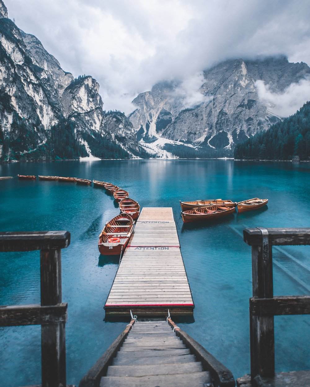 wooden dock leading out to a bright blue, icy lake surrounded by snowy mountains