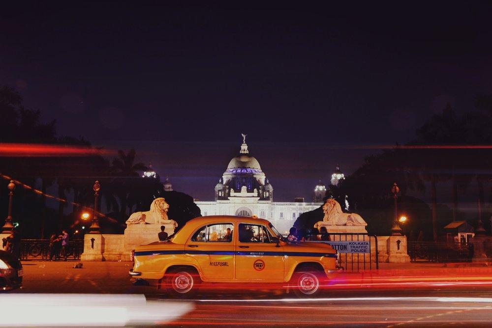 taxi driving by building at night in kolkata india