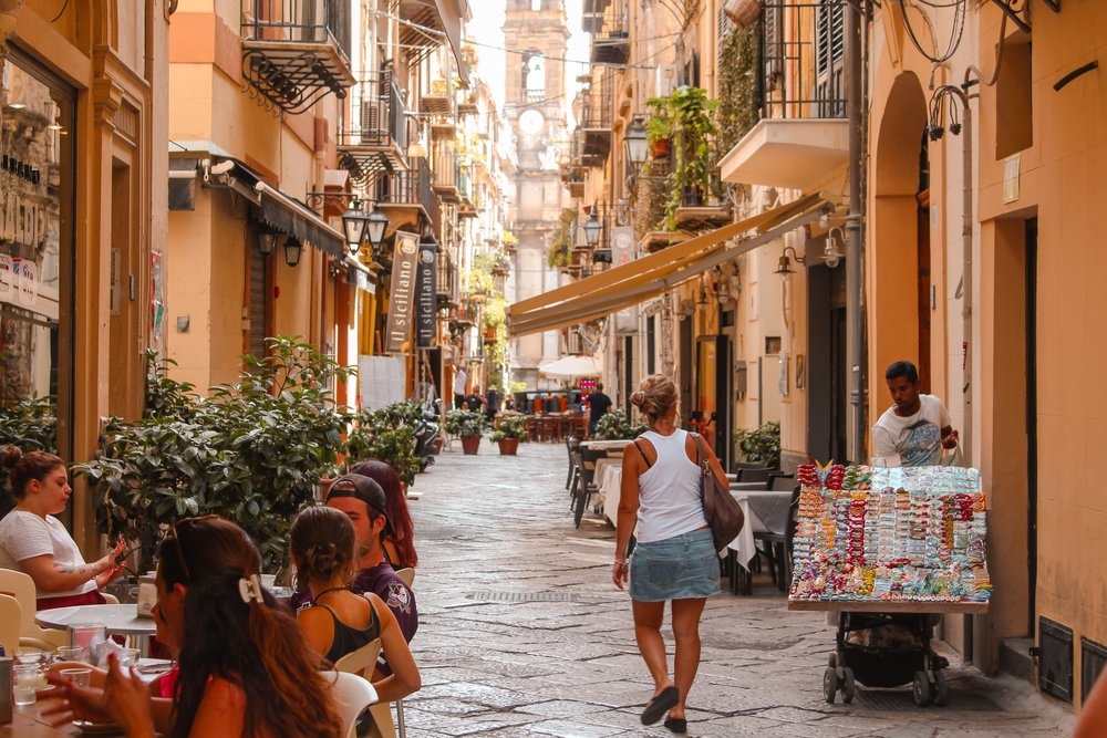 beautiful sunny street in palermo sicily with people sitting outside