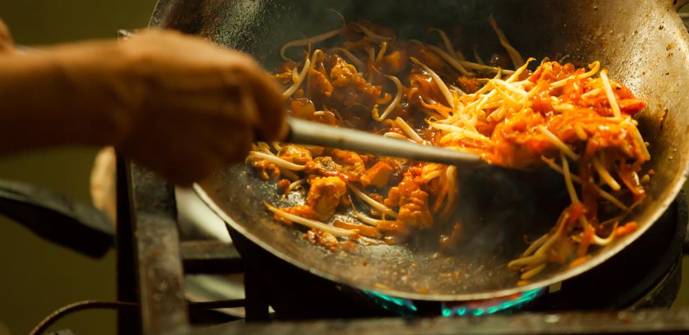 pad thai in wok being stirred looking tasty