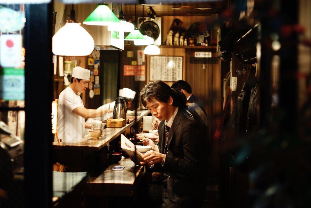 japanese man sits at a sushi bar in tokyo reading the menu
