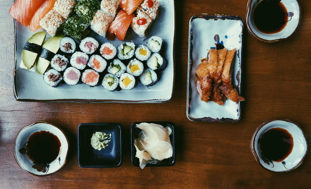 a variety of colorful sushi laid out on a platter with soy sauce in Tokyo Japan