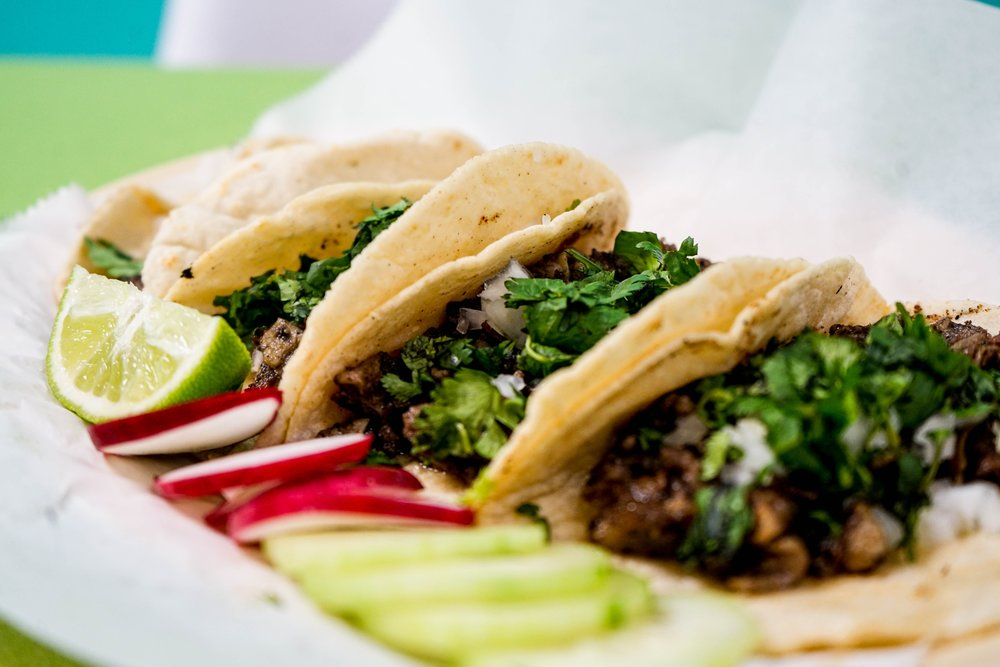three tacos on a plate with limes in mexico city