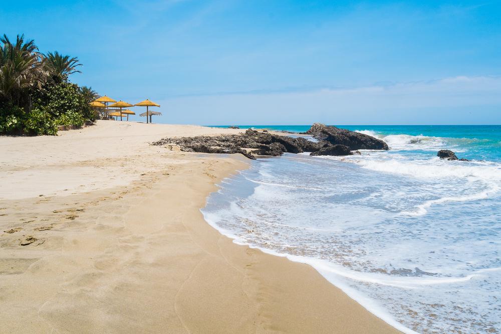 waves crashing onto rocks on beach with umbrellas in the distance in mancora peru