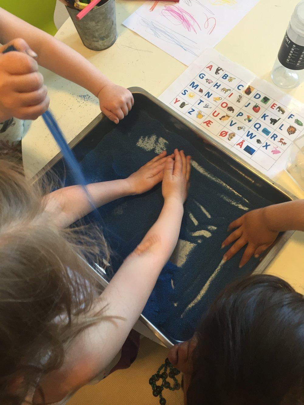 Barna tegner bokstaver. Sanden sklir utover, dekker over, den sprer seg. Sanden innbyr til ekspressivitet.