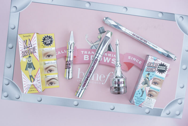 A selection of brow products form Benfit laid out on a pink background