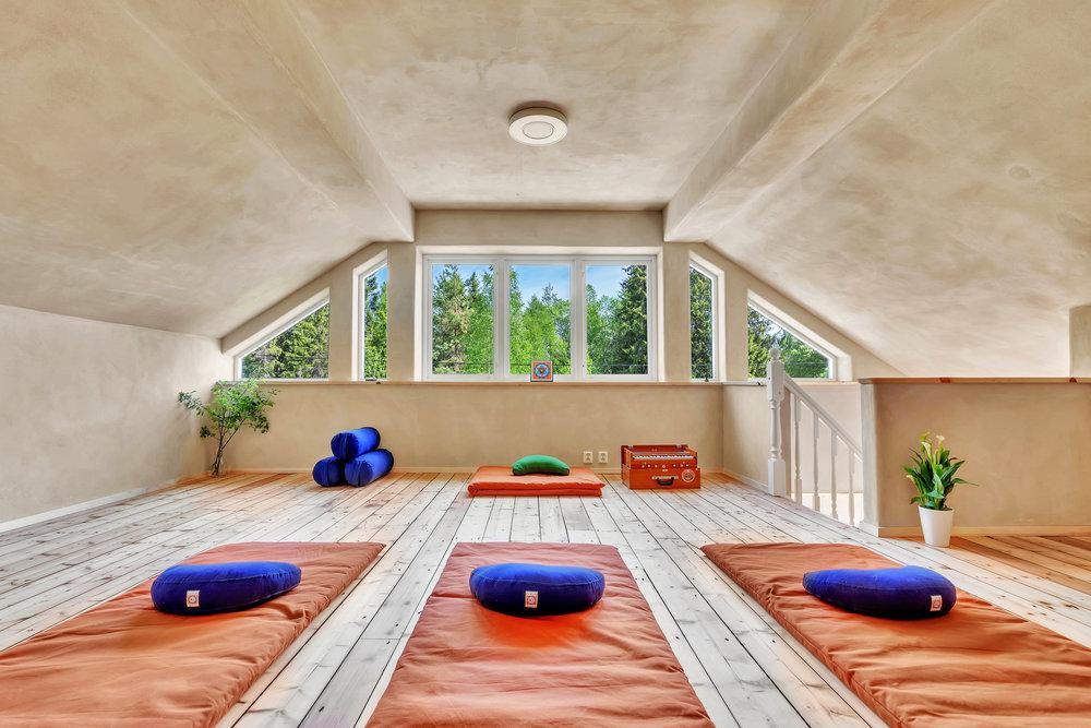 Yogarommet Anahata på Trautskogen, utstyrt med tykke og tynne matter, puter og tepper.