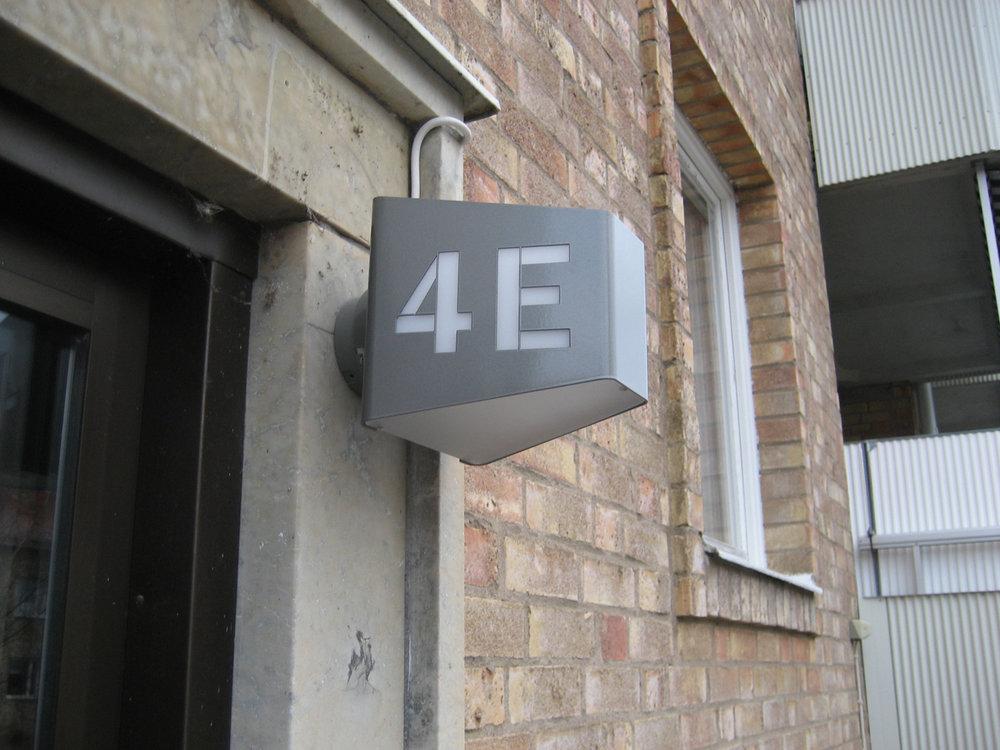 A.01 - Armatur: A.01 med laserutskurna husnummer.Projekt: BRF Skogåsen, Västerås.Arkitekt: Ark 1 Arkitektkontor AB.