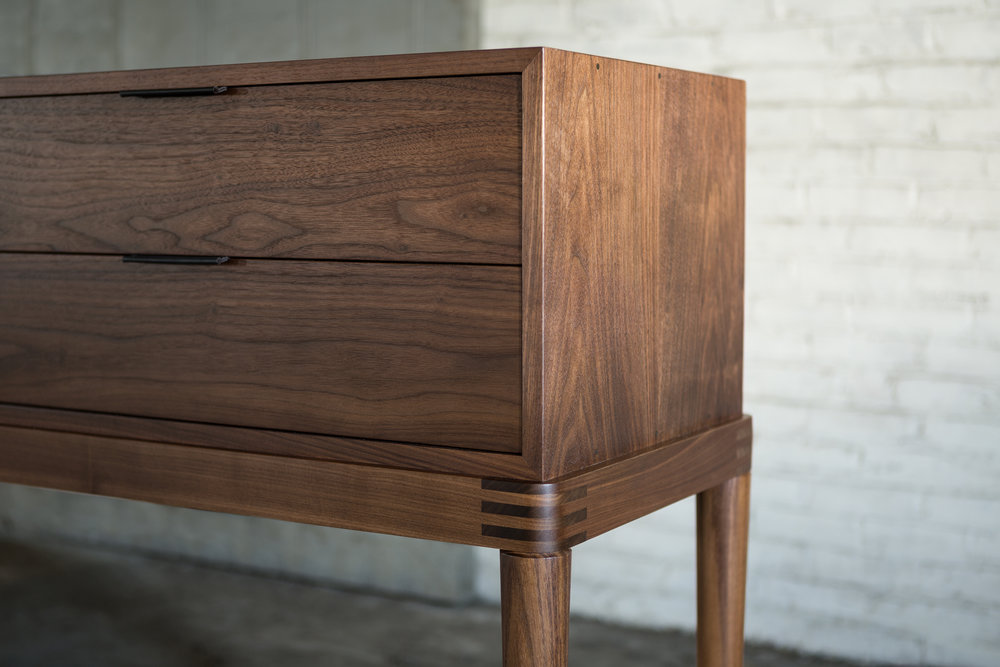 > Detail of Cumberland Sideboard; visible joinery and hand-stitched leather drawer pulls.