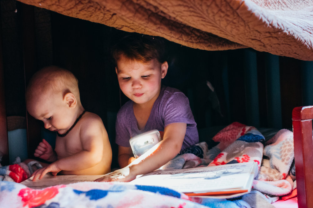 Two small red haired children sitting on a bed reading books under a blanket with light provided by a cellphone.