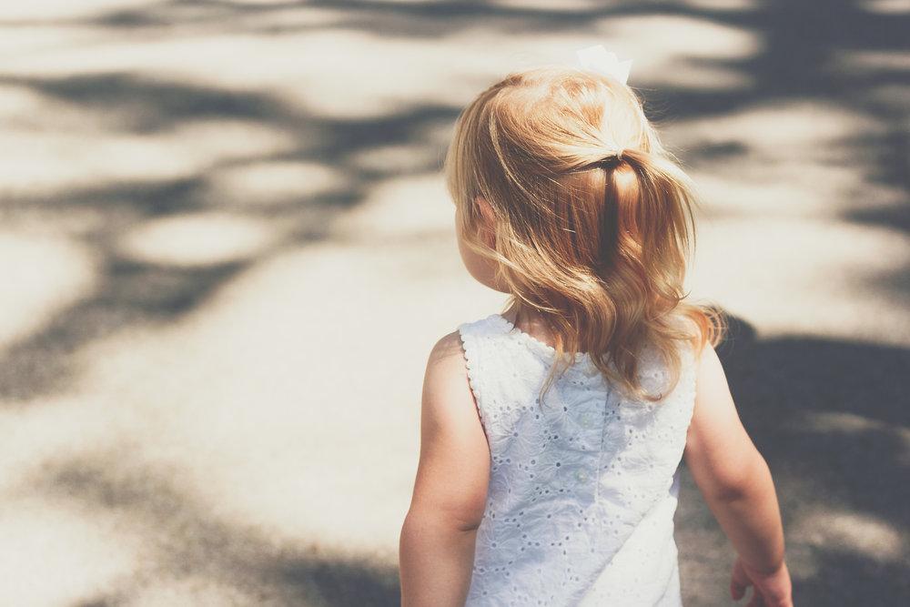 Blond hair girl in white dress walking in the sunshine
