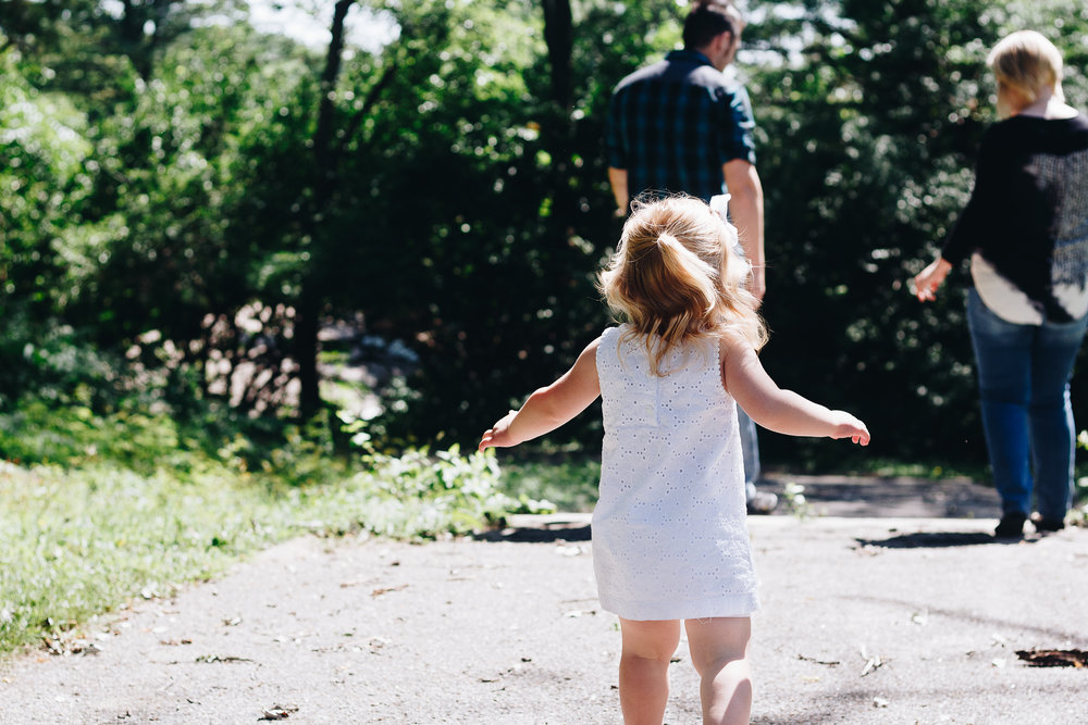 blond hair girl in white dress with back facing photo walking to her parents.