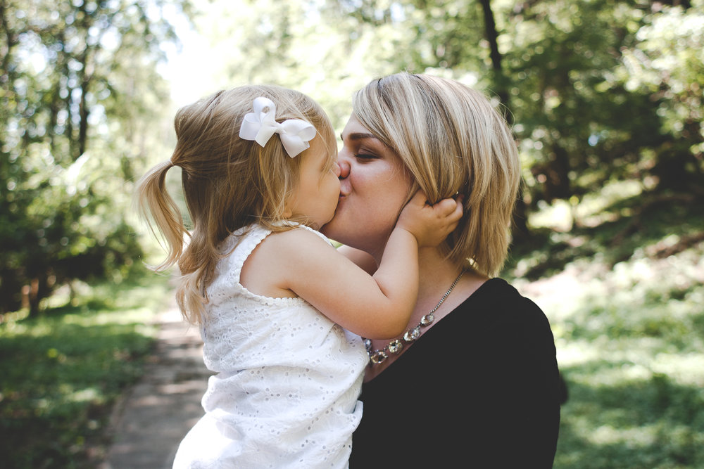 Blonde haired girl dressed in white giving kisses and squeezing the face of a blonde haired woman.