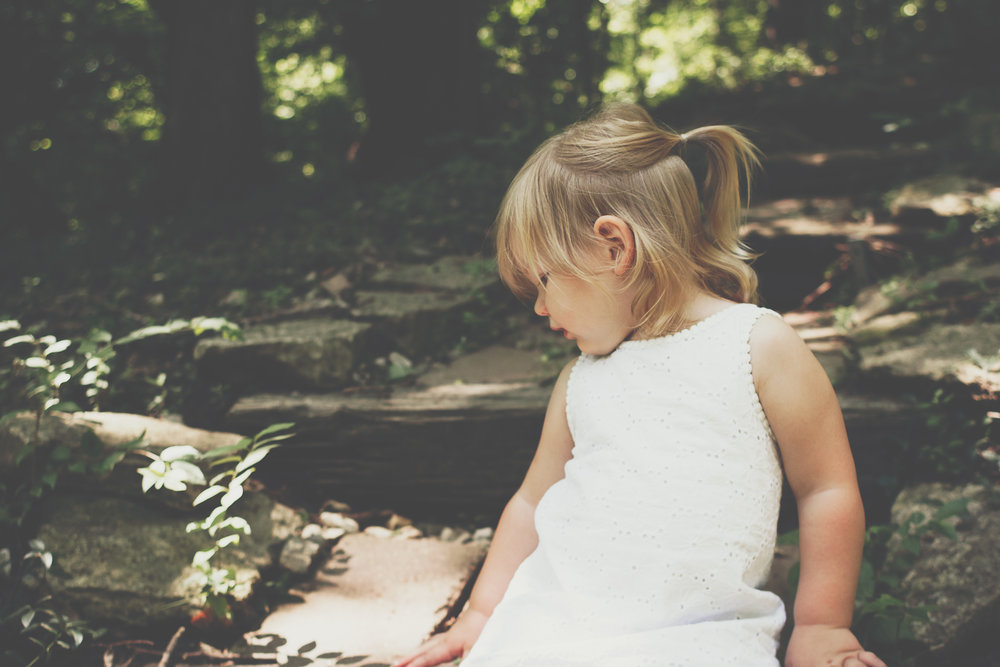 Blonde haired little girl dressed in white slightly faced a way from the camera looking over her shoulder.