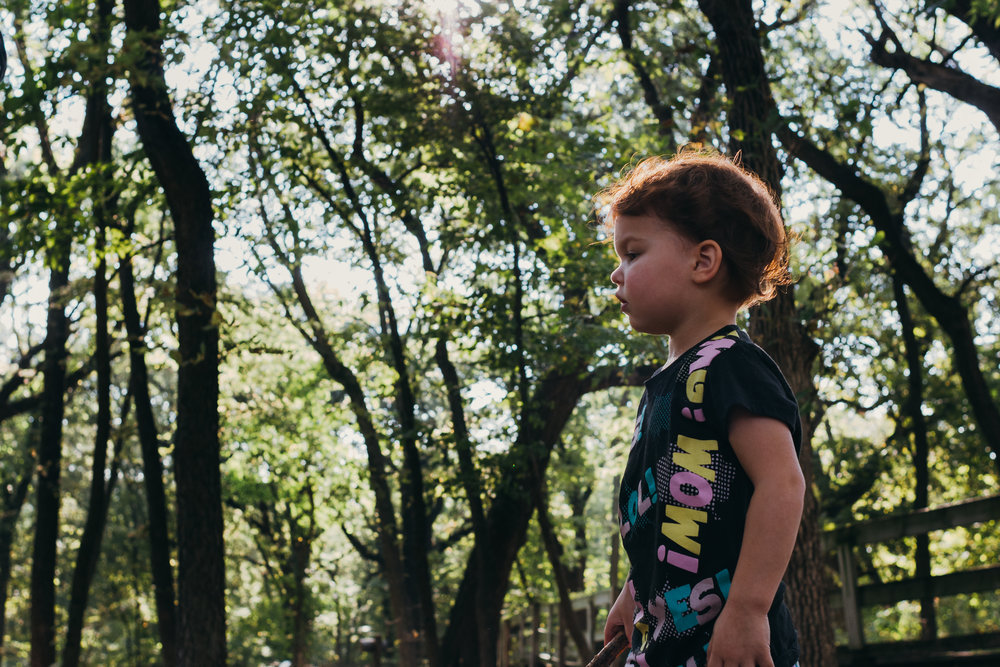 Profile of a red haired little girl in a black shirt surrounded by big trees.