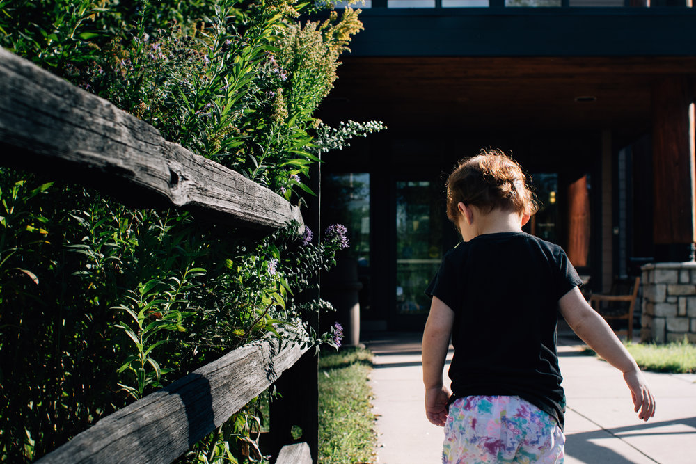 Red haired little girl in a black shirt walking up to a building with her back facing the camera.