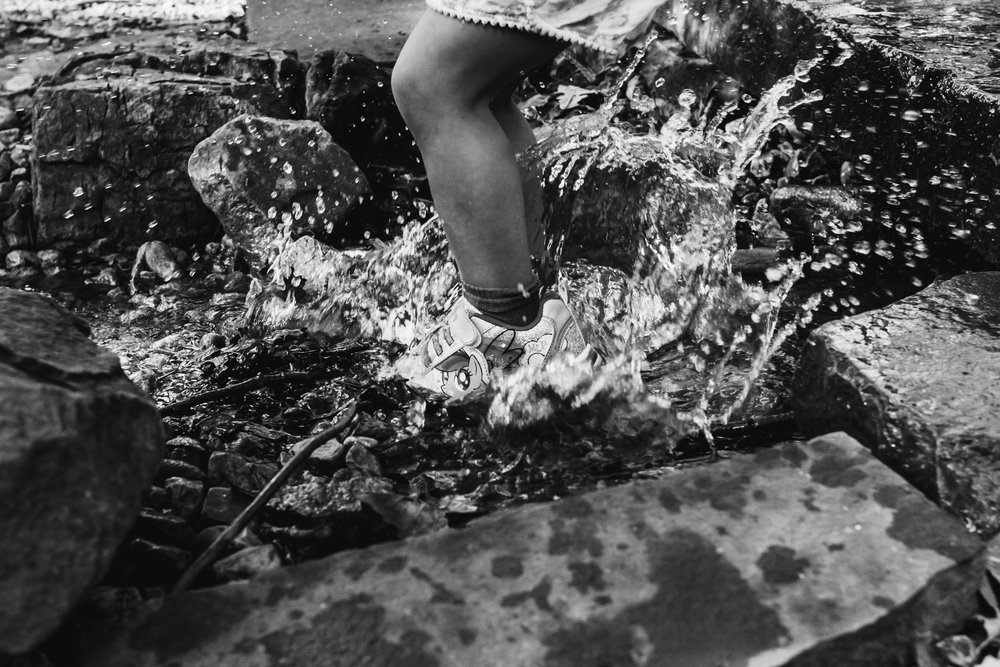 black and white photo of a girl wearing my little pony shoes splashing in a small pond in a nature center.