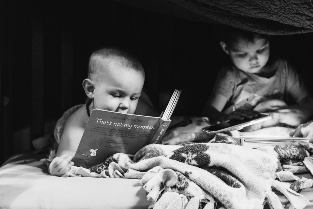 Two young children reading two different books on a bed under a blanket