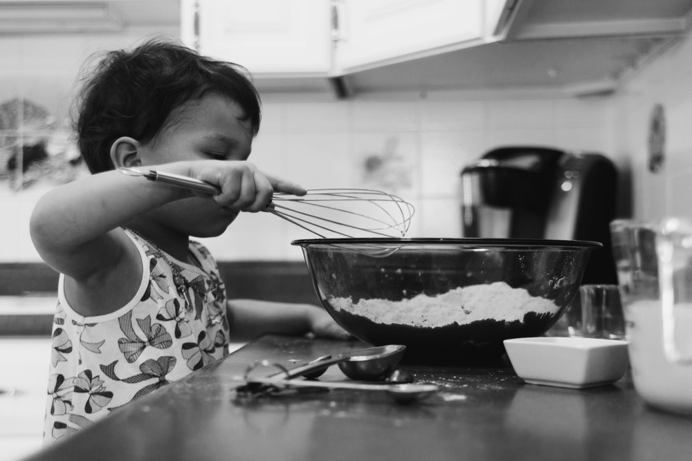 Black and white photo of a young girl getting ready to mix a clear bowl full of flour.