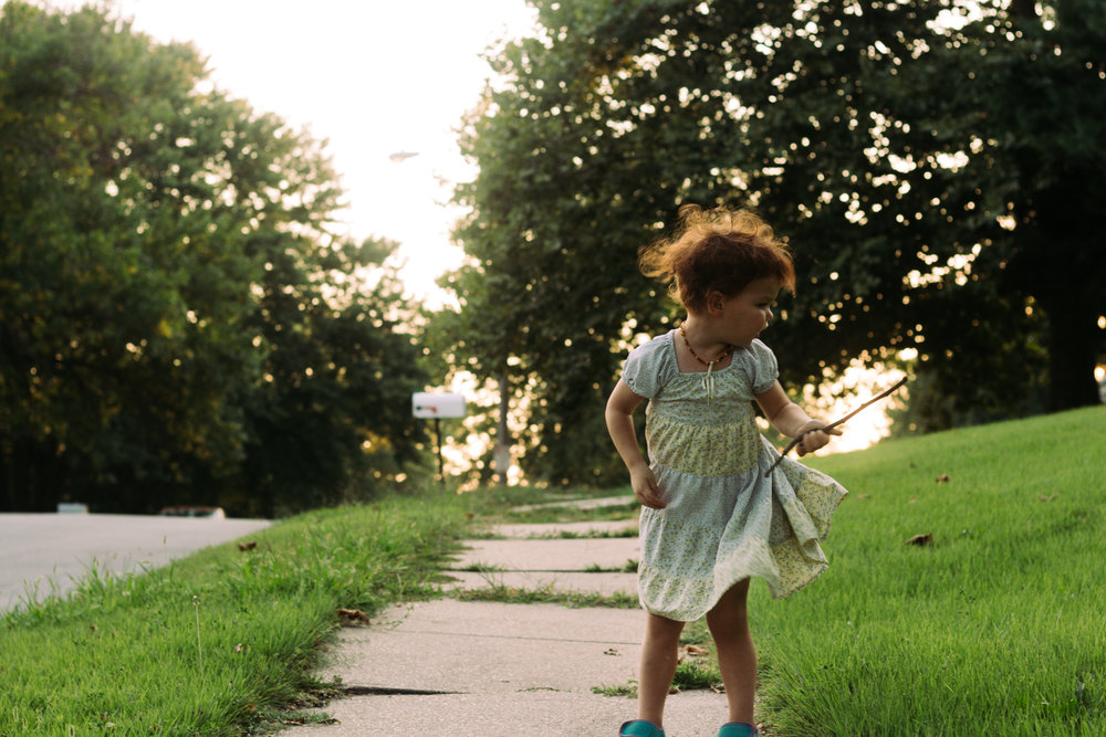 Young red haired girl in a blue and yellow dress with a floral pattern twirling around on a sidewalk.