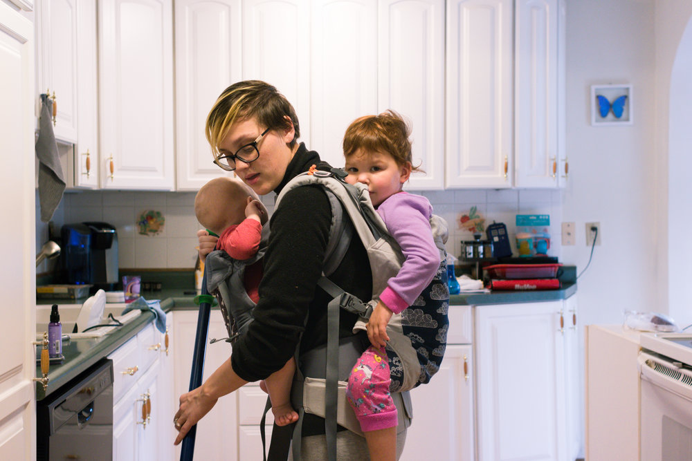 A white woman tandem carrying two children, one boy, one girl, in two different soft structured carriers while sweeping her kitchen.