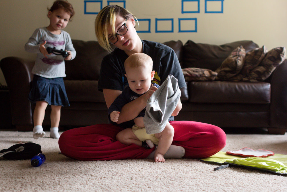 a white woman in front of a brown couch changing a baby boy into a new outfit with a young red-haired little girl standing behind her holding a PlayStation controller.