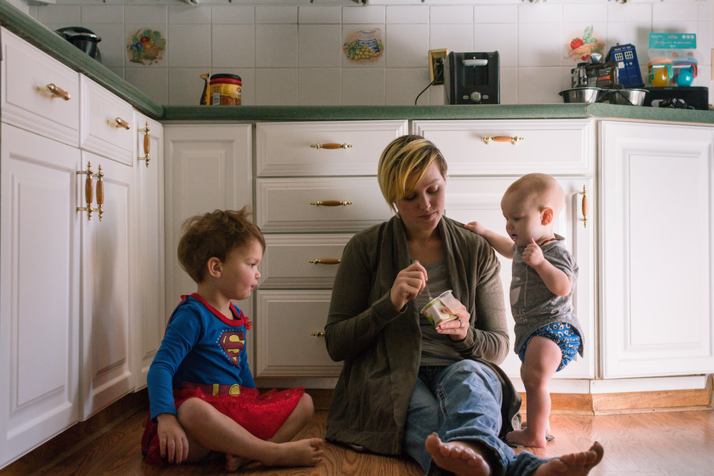 A white woman sitting on the floor of her kitchen with two kids surrounding her while she eats a yogurt.