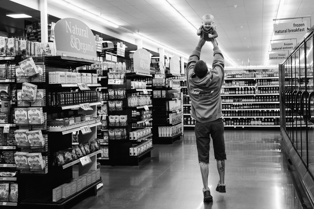 White man in a sweatshirt holding a white baby boy high in the air while walking down an isle in the gorcery store.