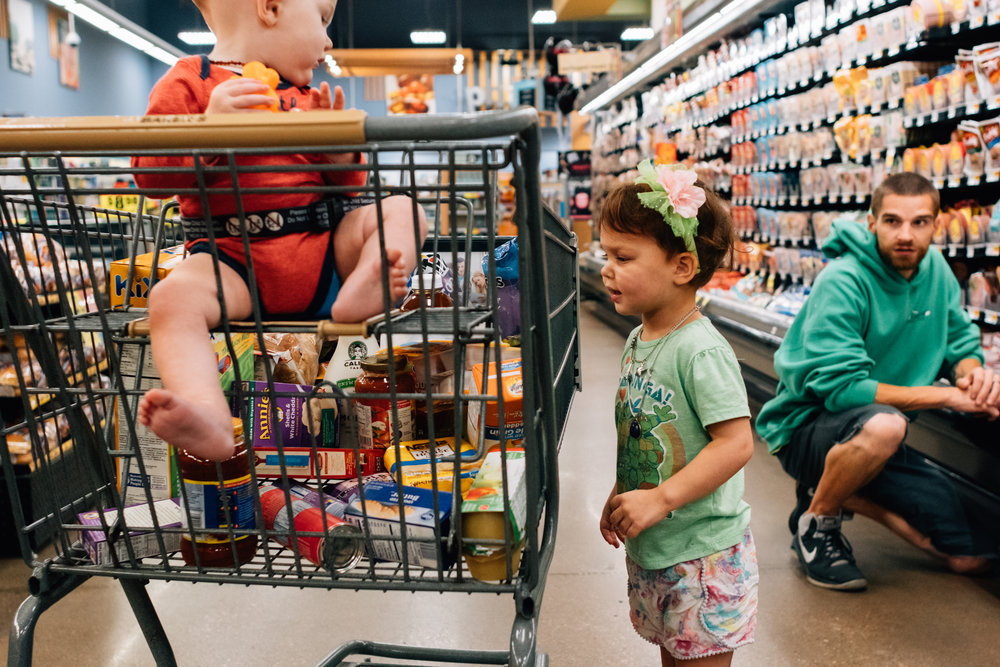A colorful photo of a white red haired girl looking into the side of a grocery cart while her brother and father watch.