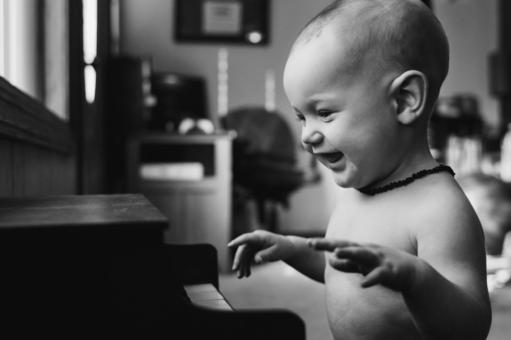 A black and white photo of a white baby boy smiling down at a small vintage piano.