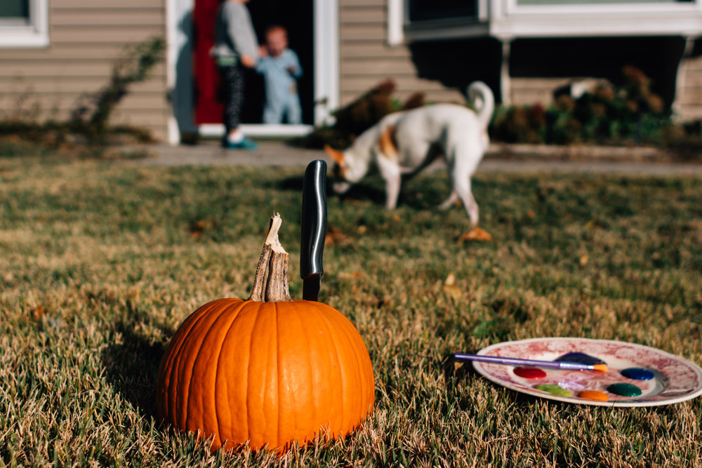 A photo of a pumpkin with a knife in it sitting in front of a grey house with two kids and a small white dog in the background.
