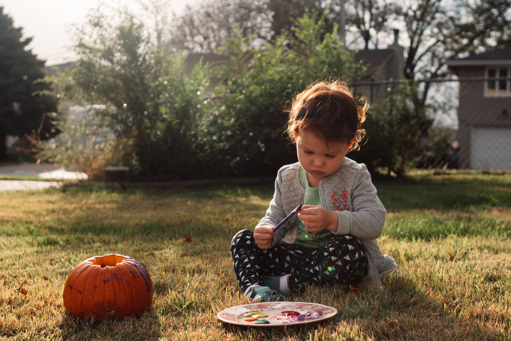 A photo of a red haired little white girl painting her small pumpkin outside.