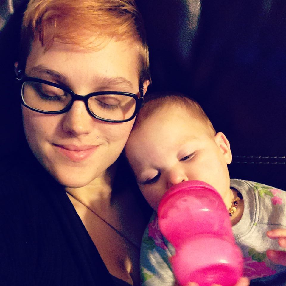 A white woman holding a white red haired baby girl drinking out of a pink sippy cup.